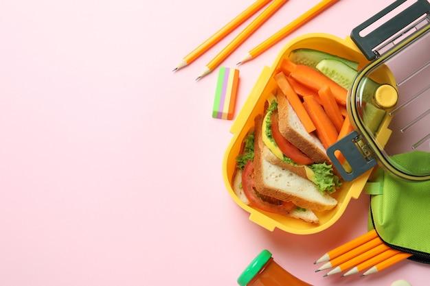 Lunch box con cibo gustoso su sfondo rosa