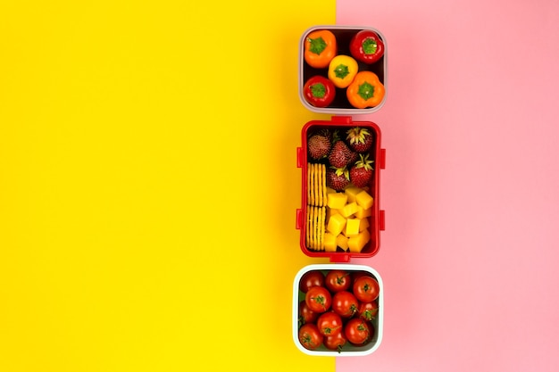Scatole per il pranzo con biscotti pezzi di formaggio fragole pomodori concetto di spuntino sano vista dall'alto