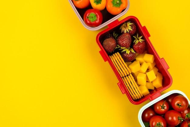 Scatole pranzo con biscotti pezzi di formaggio fragole pomodori e peperoni su un giallo