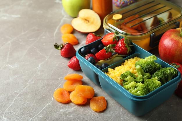 Scatole per il pranzo con cibo gustoso su un tavolo grigio strutturato
