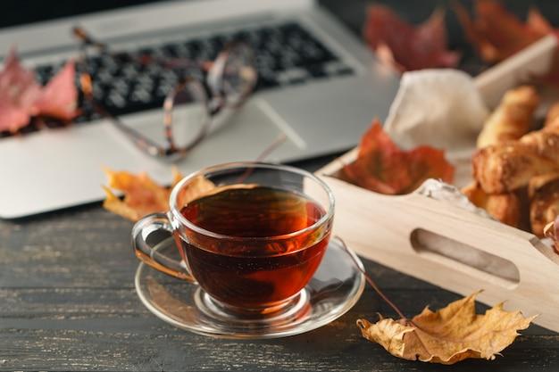 Pranzo in ufficio a casa con tè e biscotti, computer portatile sul tavolo