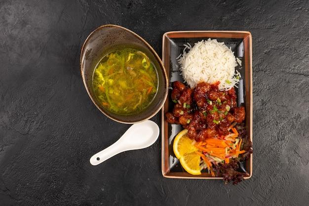 Menu del pranzo di zuppa di verdure e piatto di carne calda con riso e verdure fresche come contorno. due piatti asiatici in piatti tradizionali insoliti su un tavolo di pietra nera.