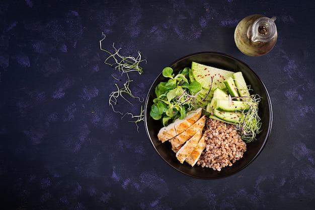 Insalata di pranzo. ciotola del buddha con porridge di grano saraceno, filetto di pollo alla griglia, insalata di mais, microgreens e daikon. cibo salutare. vista dall'alto, in alto