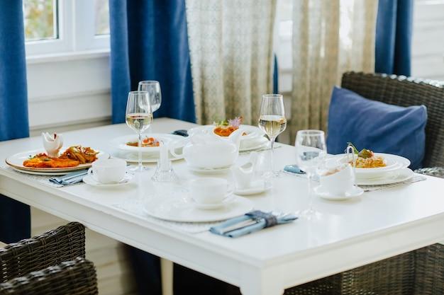 Tovaglia pranzo con cibo e bicchieri di vino bianco con servizio da tè nel ristorante.