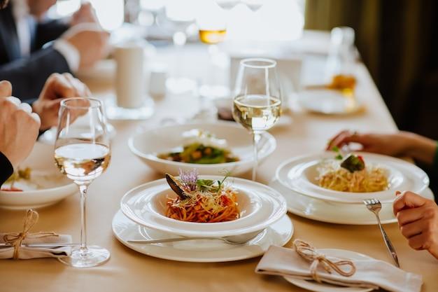 Tovaglia da pranzo con vino bianco e spaghetti in ristorante.