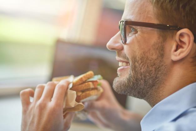 L'ora di pranzo immagine ravvicinata di un giovane felice che mangia un panino mentre lavora in remoto al bar prendendo un