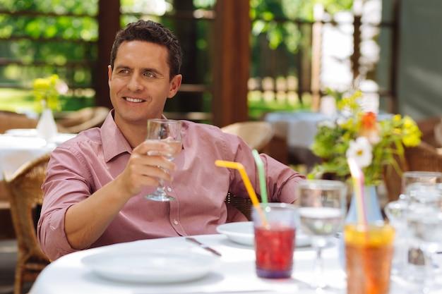 Ora di pranzo. bell'uomo dai capelli scuri che sorride ampiamente mentre si gode l'ora di pranzo sulla terrazza estiva