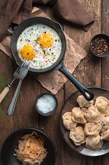 Pranzo con uova fritte e gnocchi su fondo in legno. vista dall'alto, orientamento verticale. il concetto di cucina.