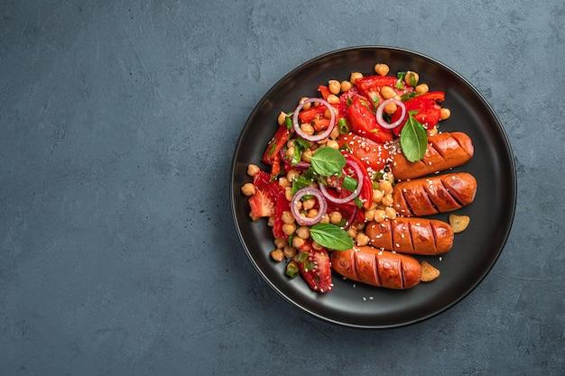 Pranzo con insalata di verdure con ceci e pomodori e salsicce su fondo scuro