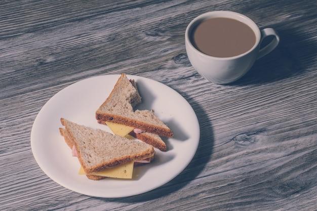 Pranzo di lavoro. primo piano di un panino al formaggio morso su un piatto rotondo bianco e una tazza di caffè caldo