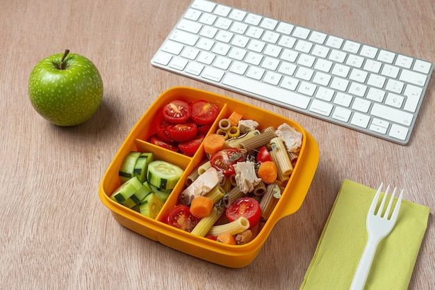 Pranzo al posto di lavoro pasta sana con tonno, pomodorini, carote, cetrioli nella scatola del pranzo sul tavolo di lavoro. cibo domestico per il concetto di ufficio
