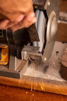 Liutaio che usa la smerigliatrice per preparare la parte in metallo