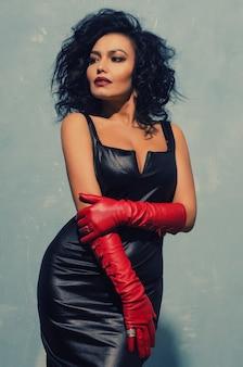 Lussuosa donna asiatica in posa in abito di pelle nera e guanti rossi. dominant fetish lady.