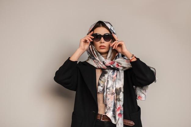 Lussuosa giovane donna attraente con labbra sexy con elegante sciarpa di seta sulla testa in cappotto nero alla moda in occhiali da sole alla moda in posa vicino al muro della città. elegante modello di moda ragazza urbana all'aperto.