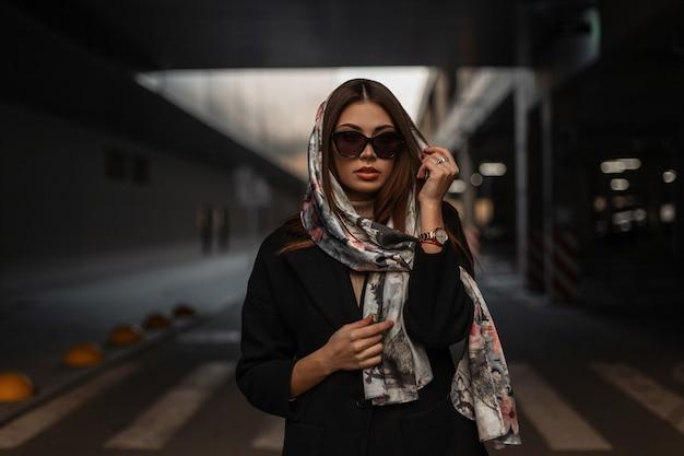 Lussuosa giovane donna attraente con labbra sexy con elegante sciarpa di seta sulla testa in cappotto nero alla moda in occhiali da sole alla moda in posa sulla strada della città. elegante modello di moda ragazza urbana all'aperto