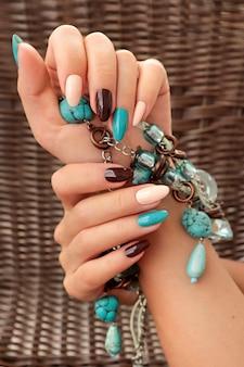 Lussuosa manicure marrone beige con disegni turchesi su unghie lunghe con accessorio.