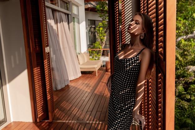 Lussuosa bionda in un abito a pois nero con gli occhi chiusi in posa vicino a una porta di legno e un'ombra cade sul suo viso e corpo.