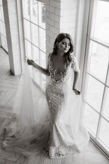 Una sposa lussuosa in un abito da sposa al mattino nel suo interno. foto in bianco e nero.