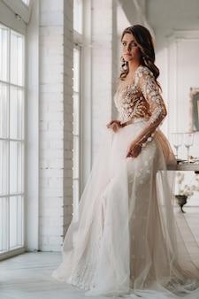 Una sposa lussuosa in un abito da sposa al mattino nel suo interno