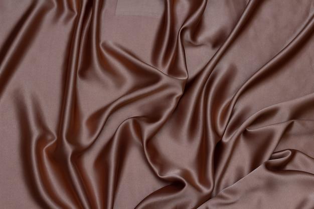 Onde di raso o seta marroni eleganti di lusso per sfondo astratto