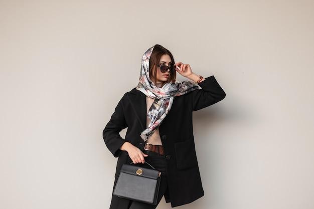 La giovane donna elegante lussuosa in scialle di seta sulla testa in cappotto nero alla moda con una borsa di cuoio alla moda raddrizza gli occhiali da sole dell'annata vicino alla parete all'interno. bella ragazza professionale moderna.