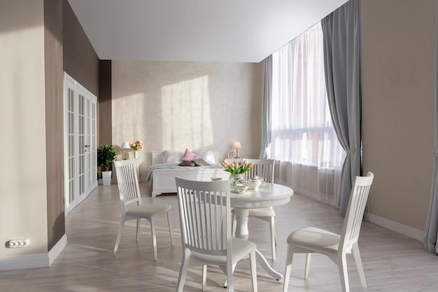 Interni lussuosi e costosi di un appartamento a pianta aperta in colori chiari. camera da letto moderna ed elegante con design minimale, zona pranzo e spazio per gli ospiti.