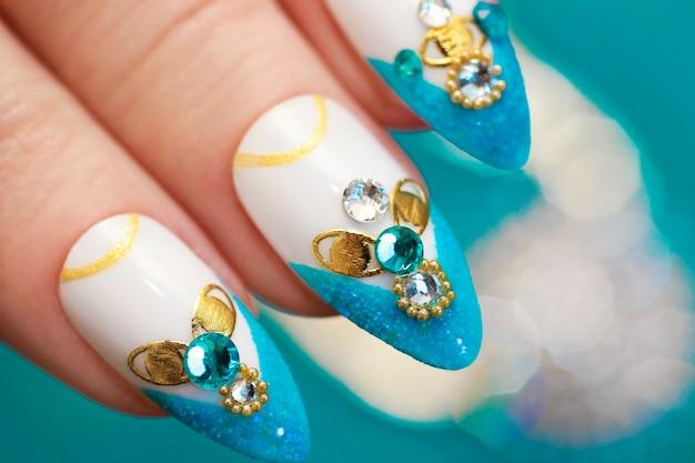 Lussuosa manicure francese blu sabbia glamour con strass, boulongne e primo piano delle unghie delle donne placcate in oro.