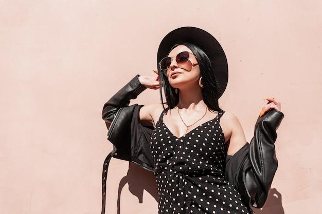 Lussuosa giovane donna affascinante in eleganti occhiali da sole in giacca di pelle in bel vestito raddrizza il cappello in giornata di sole. attraente ragazza alla moda in eleganti abiti estivi neri gode della luce del sole sulla strada
