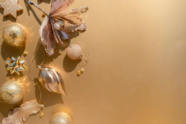 Lussuoso piatto di natale in oro con vari ornamenti su uno sfondo dorato con spazio per le copie