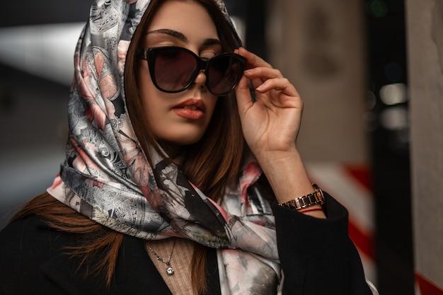 Modello di lusso piuttosto giovane donna in una sciarpa di seta elegante alla moda sulla testa con labbra sexy raddrizza eleganti occhiali da sole scuri. ragazza attraente del ritratto fresco d'avanguardia. bella signora d'affari.