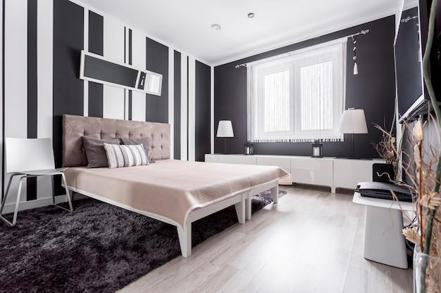 Lussuosa camera da letto moderna con carta da parati a righe e letto con testiera