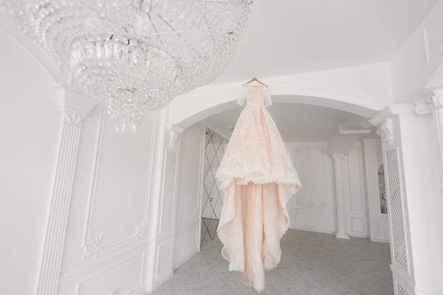 Lussuoso abito da sposa color pesca appeso a un lampadario in una stanza bianca