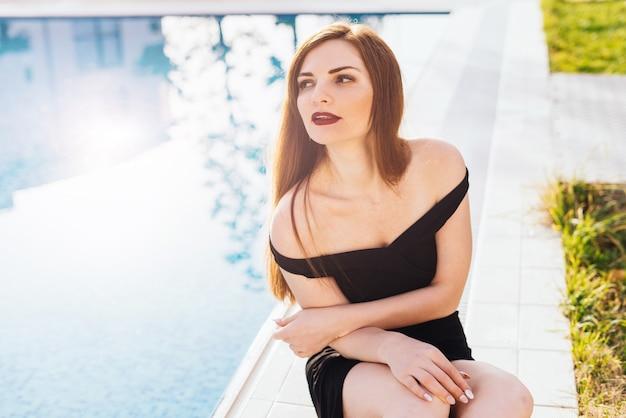 Una lussuosa donna sexy in un abito nero si siede vicino alla piscina blu, gode di un ricco riposo e del sole
