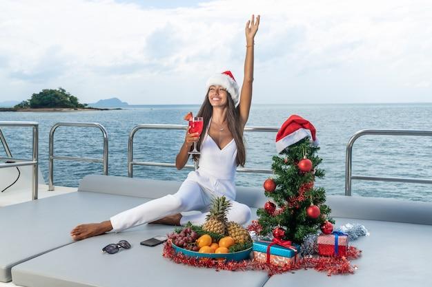 Lussuosa donna in abito bianco e cappello da babbo natale festeggia il nuovo anno su una crociera in yacht tropicale.
