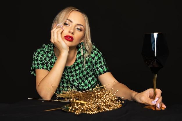La giovane donna bionda lussuosa in vestito verde su fondo nero è annoiata sulla dieta. concetto di disturbo alimentare. foto in studio