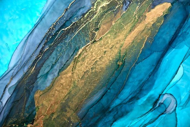 Sfondo astratto di lusso in tecnica di inchiostro ad alcool, pittura liquida oro blu indaco, macchie acriliche sparse e macchie vorticose, materiali stampati