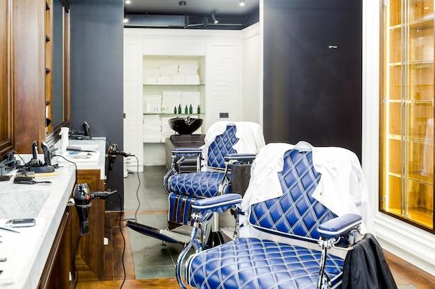 Interno del negozio di barbiere di lusso, mobili costosi blu, finiture in legno, soffitto nero alla moda