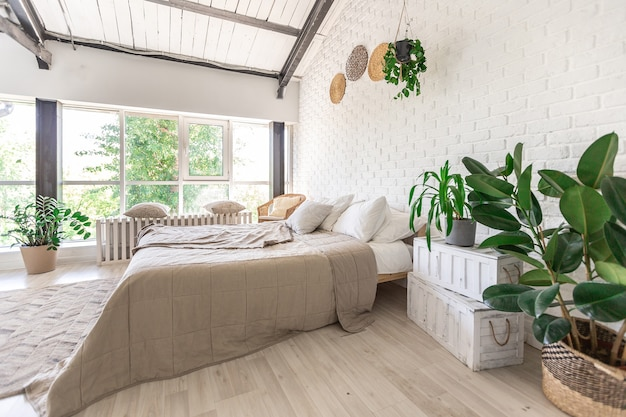 Design della camera da letto di lusso in un cottage rustico in stile minimalista. pareti bianche, finestre panoramiche, elementi decorativi in legno sul soffitto, altalene di corda nel mezzo di una stanza spaziosa.