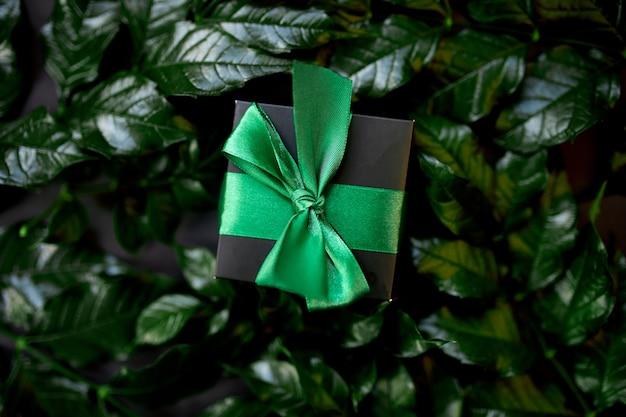 Confezione regalo nera di lusso con nastro verde su sfondo scuro con foglie sui lati, layout creativo, piatto, concetto di natura