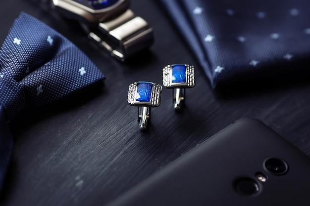 Gemelli da uomo di lusso blu moda. accessori per smoking, farfalla, cravatta, fazzoletto, orologio stile e smartphone.
