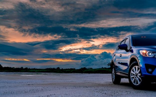 L'automobile blu di lusso di suv ha parcheggiato su terra accanto alla foresta tropicale con il bello cielo dell'alba. auto nuova con sport e design moderno. car drive per avventura su strada. industria automobilistica.