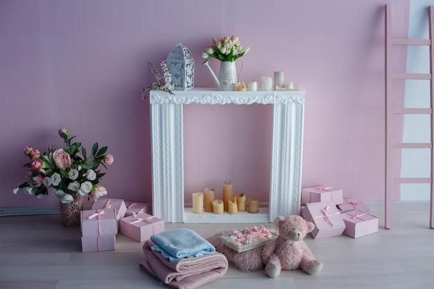 Interni bianchi luminosi puliti di lusso. una stanza spaziosa con luce solare e fiori in vasi, con un caminetto decorativo, graziosi plaid rosa e un vaso con marshmallow. idea e concept della cameretta di una ragazza