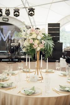 Lusso, elegante disposizione dei tavoli per ricevimenti di nozze, centrotavola floreale.