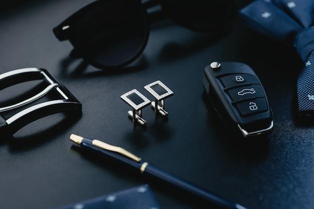 Gemelli da uomo di moda di lusso, occhiali, papillon, penna e chiavi della macchina su sfondo scuro.