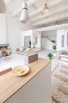 Lussuoso appartamento dal design moderno e alla moda con un layout gratuito in uno stile minimalista. camera spaziosa molto luminosa con pareti bianche ed elementi in legno