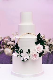 Torta bianca a quattro livelli di lusso con fiori, dessert di nozze