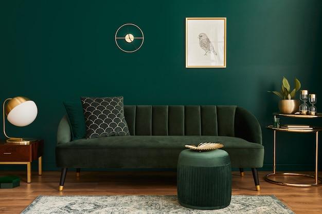 Soggiorno di lusso in casa con interni dal design moderno, divano in velluto verde, tavolino, pouf, decorazioni dorate, pianta, lampada, tappeto, cornice per poster finto e accessori eleganti. modello.
