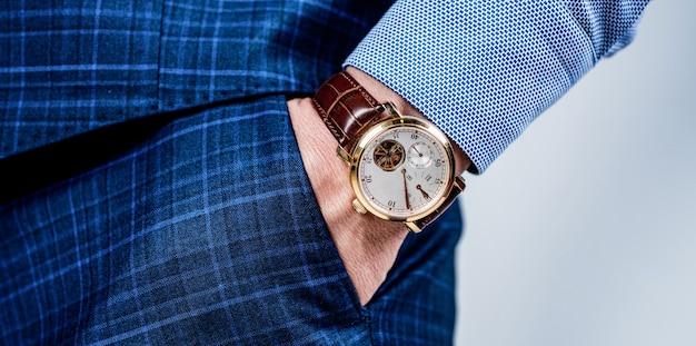 Orologio da polso maschile di lusso indossato sul braccio nella tasca dei pantaloni, tempo.