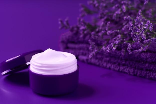 Lozione idratante di lusso o crema per il corpo in un barattolo viola su un tavolo, copia spazio per il testo.