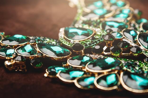 Collana di lusso con pietre preziose verdi sul velluto marrone